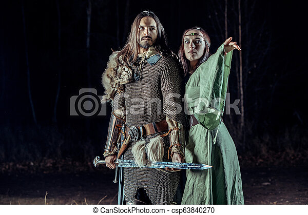 Medieval knight with his beloved lady. Dark forest on the background. - csp63840270