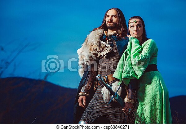 Medieval knight with his beloved lady. Evening sky on the background. - csp63840271
