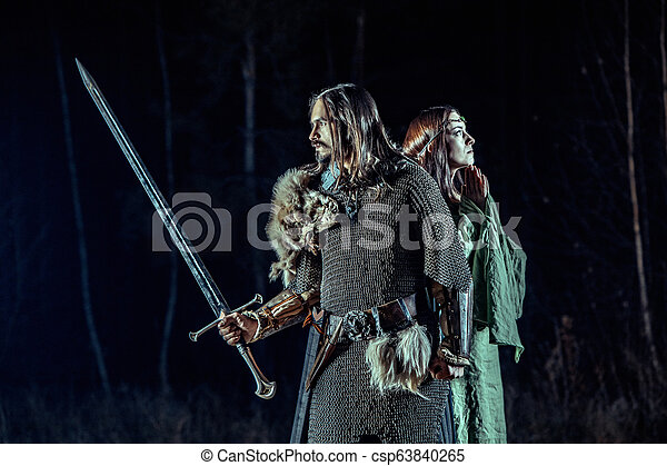 Medieval knight with his beloved lady. Dark forest on the background. - csp63840265
