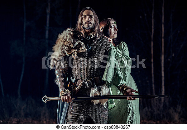 Medieval knight with his beloved lady. Dark forest on the background. - csp63840267