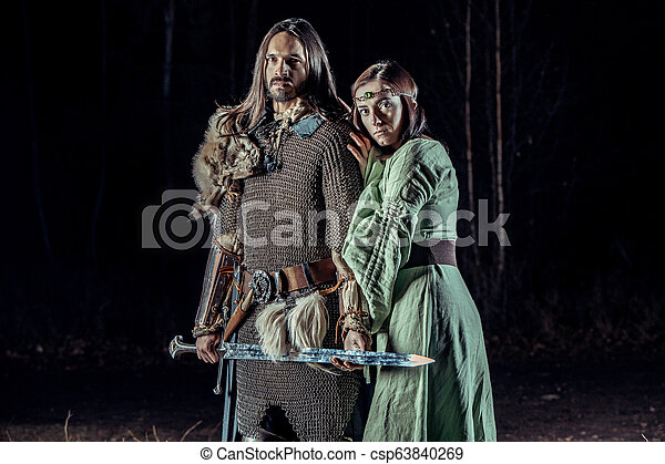 Medieval knight with his beloved lady. Dark forest on the background. - csp63840269