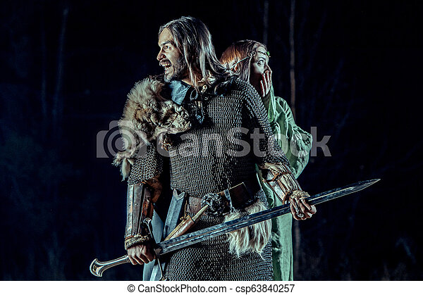 Medieval knight with his beloved lady. Dark forest on the background. - csp63840257