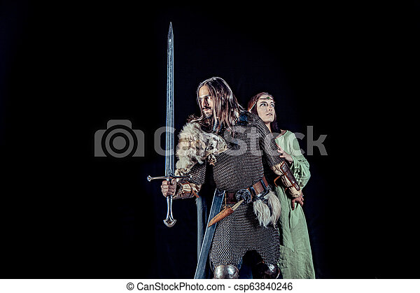 Medieval knight with his beloved lady. Dark forest on the background. - csp63840246