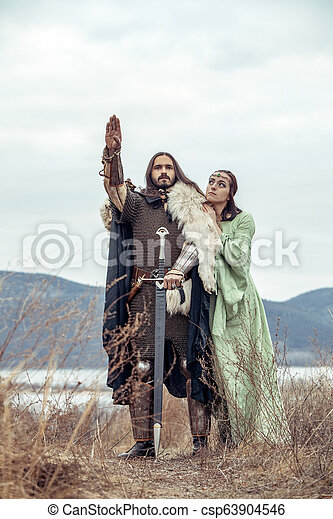 Medieval knight with his beloved lady. Evening sky on the background. - csp63904546