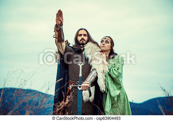 Medieval knight with his beloved lady. Evening sky on the background. - csp63904493