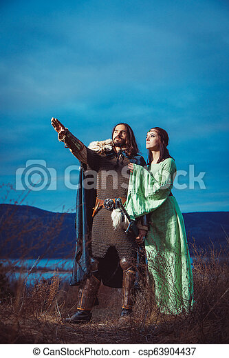 Medieval knight with his beloved lady. Evening sky on the background. - csp63904437