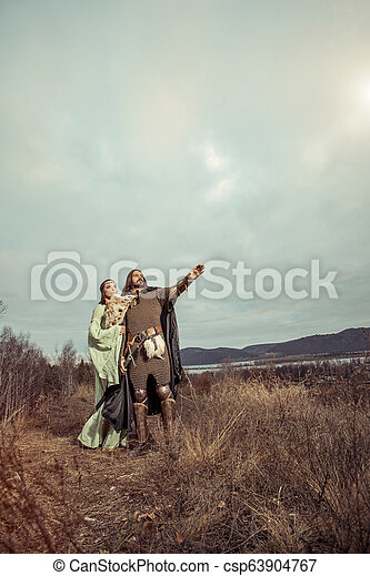 Medieval knight with lady on the sunset background. - csp63904767
