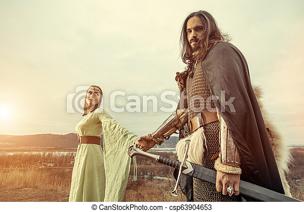 Medieval knight with lady on the sunset background. - csp63904653