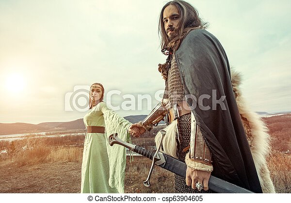 Medieval knight with lady on the sunset background. - csp63904605
