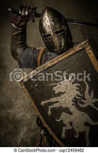 Medieval knight with sword and shield against stone wall - csp12459482