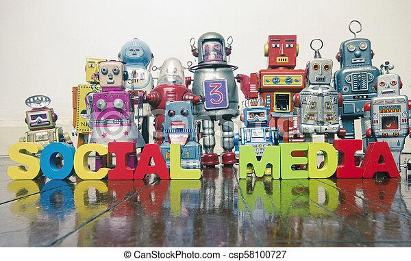 Las palabras MEDIA SOCIAL con juguetes robot retro en un suelo de madera - csp58100727