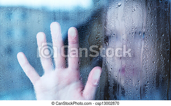 melancholy and sad young woman at the window in the rain - csp13002870