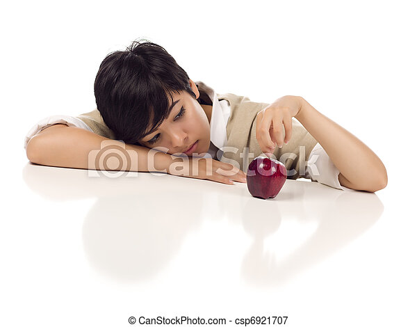 Melancholy Mixed Race Young Adult Female Sitting at White Table with Apple Isolated on a White Background - Focus is on the Apple. - csp6921707