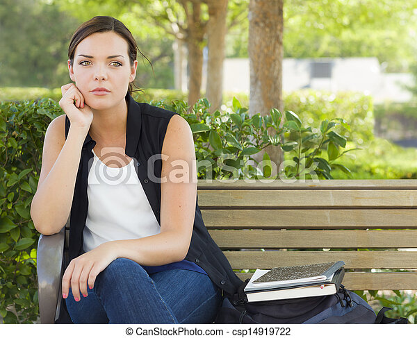 Melancholy Young Adult Woman Sitting on Bench Next to Books  - csp14919722