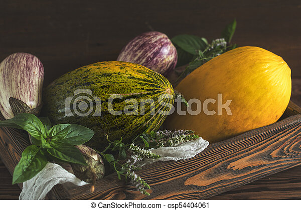 Melon, basil, mint, purple graffiti eggplants, onion and green fresh basil in a wooden box in a vintage wooden background in rustic style, selective focus, toned photo - csp54404061