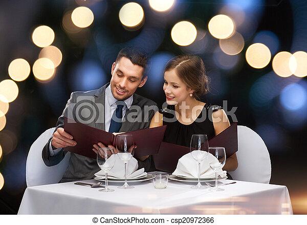 Pareja sonriente con menús en el restaurante - csp20972366