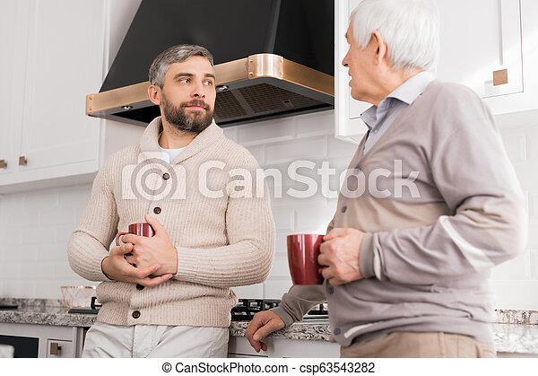 Men Chatting in Kitchen - csp63543282