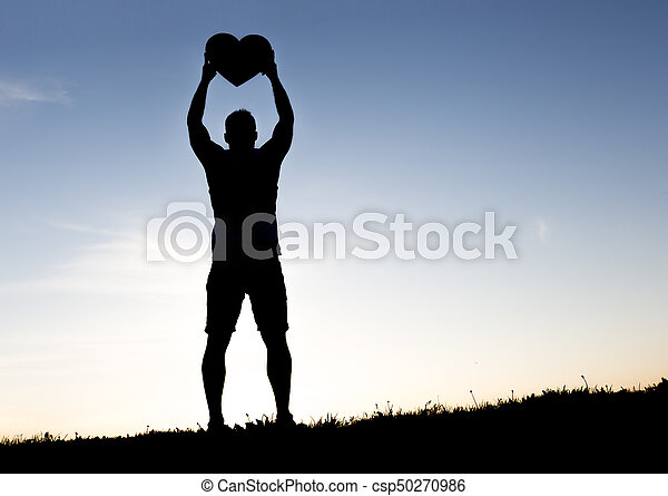 men hands holding hearts silhouette on Silhouette sunset - csp50270986