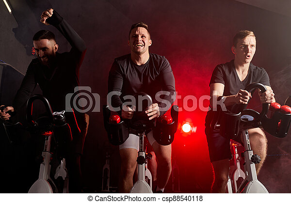 men on gym bicycle, training on a stationary bike in health club - csp88540118