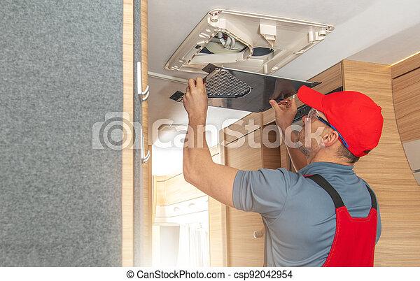 Men Repairing Air Condition Unit Inside Modern Travel Trailer - csp92042954