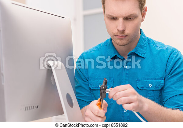 Men repairing TV cable. Confident young men cutting the network connection plug - csp16551892