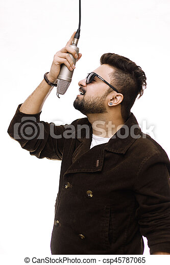 Men Wearing brown coat and glasses singing into condenser microphone - csp45787065
