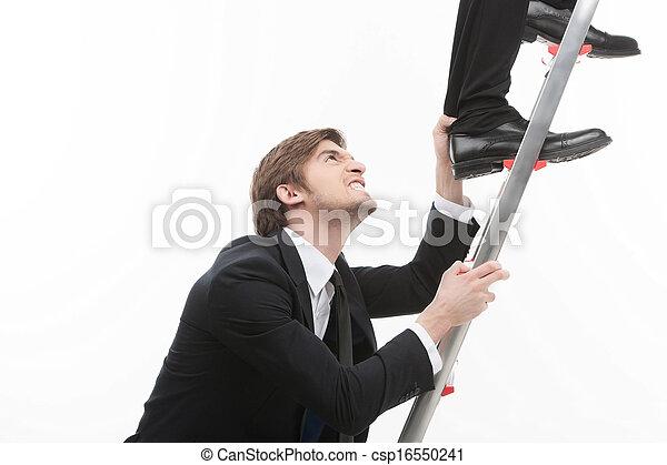 Competencia de negocios. Un joven hombre de negocios enojado agarrando a otro hombre la pierna subiendo por las escaleras - csp16550241