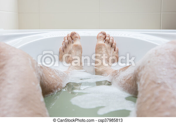 Men\'s feet in a bathtub, selective focus on toes. Men\'s feet in a ...