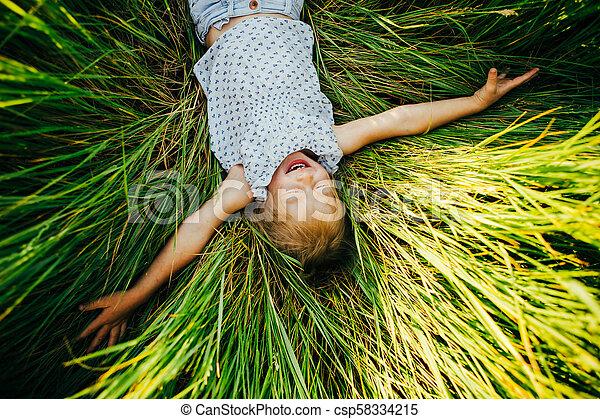 La chica está en un gran claro verde y mira a la cámara sonriendo. La mejor vista. - csp58334215