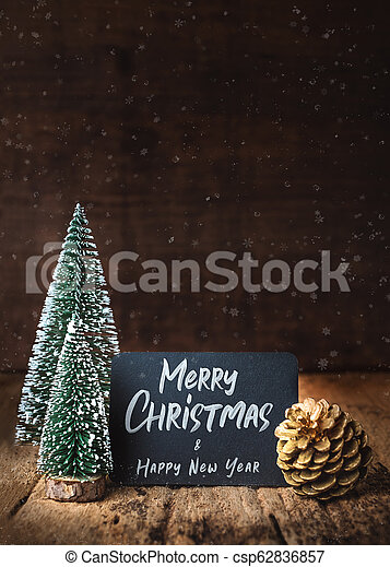 Merry Christmas and happy new year on blackboard with xmas tree and gold pine cone and snow falling on grunge wood table and dark brown wooden wall. winter holiday greeting card. - csp62836857