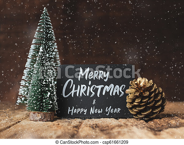 Merry Christmas and happy new year on blackboard with xmas tree and gold pine cone and snow falling on grunge wood table and dark brown wooden wall. winter holiday greeting card. - csp61661209