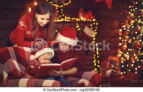 Merry Christmas Family.Merry Christmas Family Mother Father And Baby Read Book Near Tree
