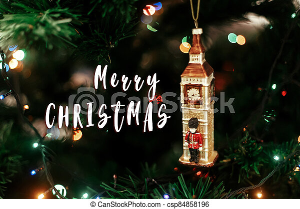 merry christmas text sign on  Queen's guard near big ben christmas ornament, cute toy soldier near golden watch clock english decoration close-up, surrounded by colorful lights - csp84858196