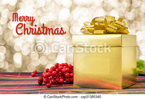 Merry Christmas word with Gold present box and ribbon on table with sparkling gold bokeh light background, Holiday concept - csp31385340