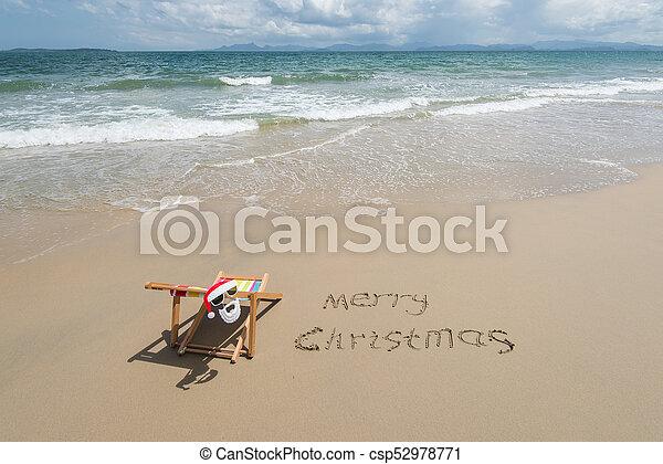 merry christmas written in sand write on tropical beachdeck chair with santa claus sunglasses - Merry Christmas Beach