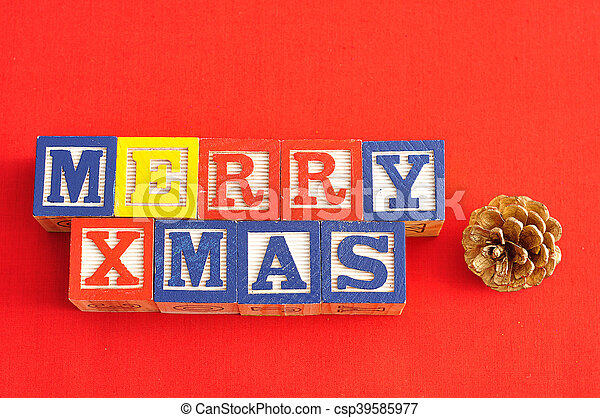 Merry Xmas spelled with Alphabet blocks and an acorn on a red background - csp39585977