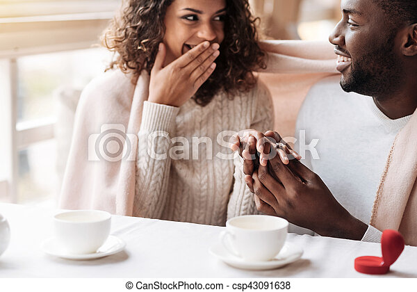 Merry young African American couple getting engaged in the cafe - csp43091638