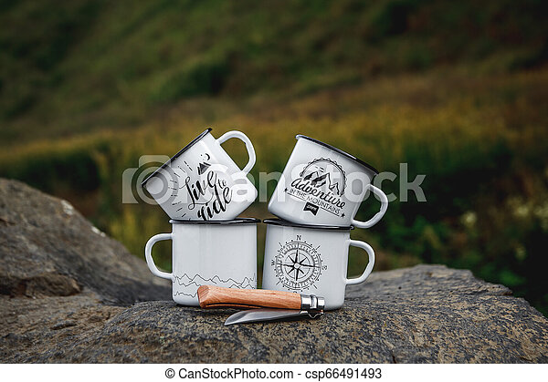 Metal cups with a tourist knife on the rock in the nature - csp66491493