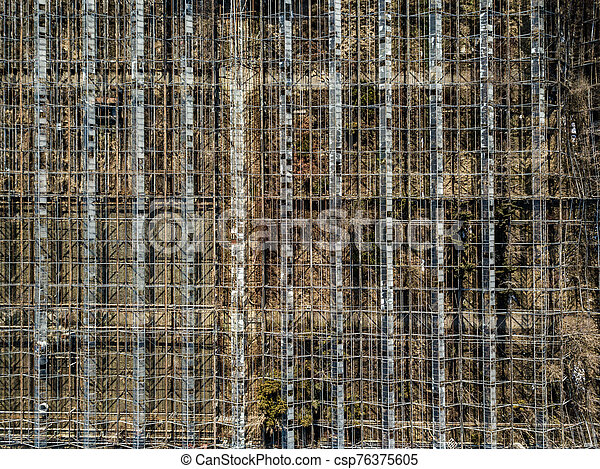 Metal framework of greenhouses on a ground of drone view. - csp76375605