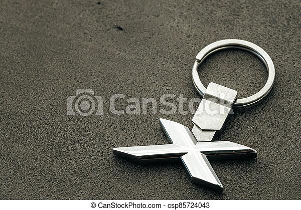 Metal letter X car key on dark concrete background - csp85724043