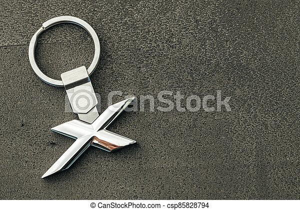 Metal letter X car key on dark concrete background - csp85828794