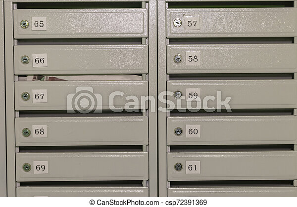 Metal mailboxes with apartment numbers painted in gray. - csp72391369