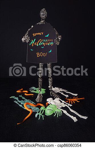 Metal mannequin holding Halloween sign - csp86060354