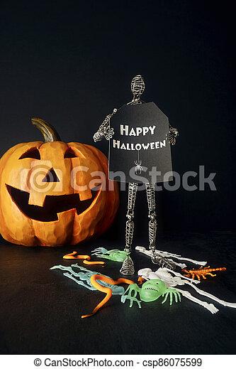 Metal mannequin holding sign with pumpkin - csp86075599