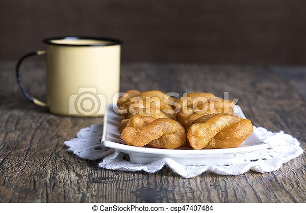 Metal mug full of coffee and a plate of koeksisters on brown wood - csp47407484