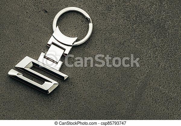 Metal number 5 car key on dark concrete background - csp85793747
