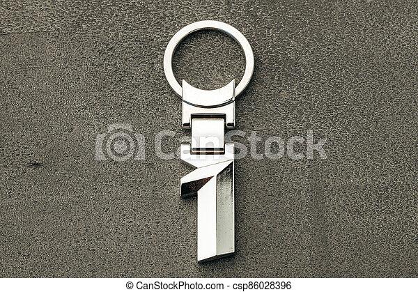 Metal number One car key on dark concrete background - csp86028396