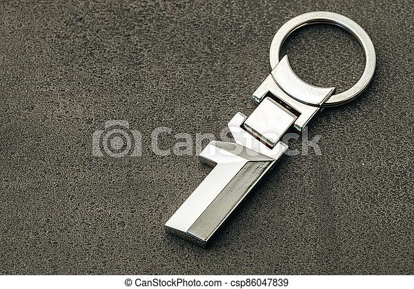 Metal number One car key on dark concrete background - csp86047839