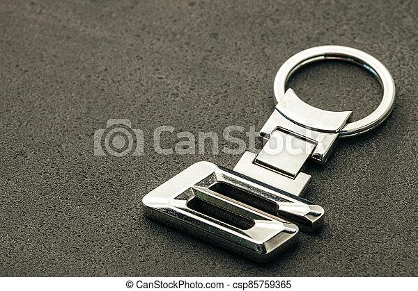 Metal number SIX car key on dark concrete background - csp85759365