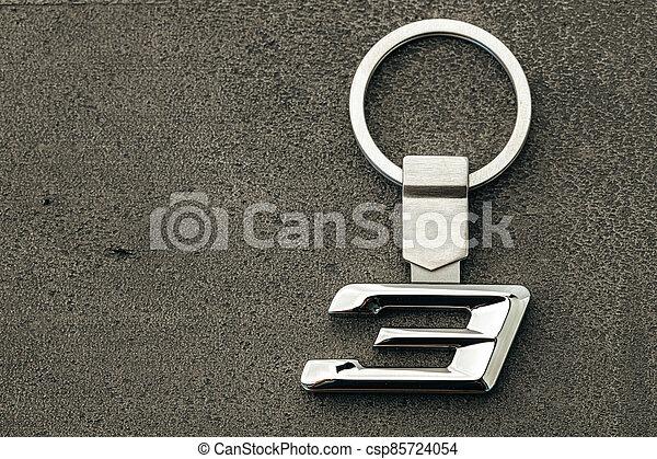 Metal number Three car key on dark concrete background - csp85724054